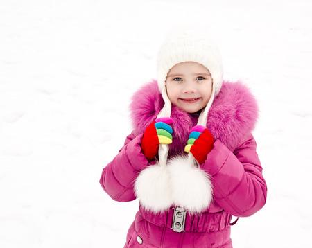 winterwear: Portrait of smiling little girl in winter day outdoor