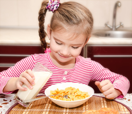 cereals holding hands: Cute little girl having breakfast cereals with milk in the kitchen Stock Photo