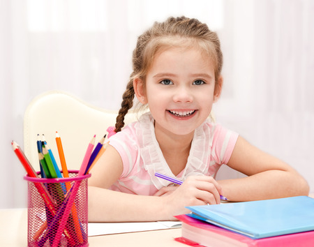 orthography: Cute smiling little girl is writing at the desk at home Stock Photo