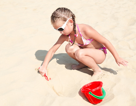 sandcastles: Cute smiling little girl playing on beach with bucket and shovel
