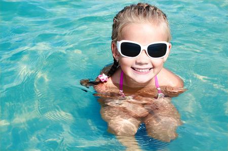 vacaciones en la playa: Adorable ni�a sonriente en vacaciones en la playa con gafas de sol