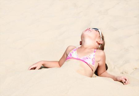 Happy cute little girl lying in sand on the beach