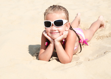 sandcastles: Happy cute little girl in sunglasses lying on the sand on the beach