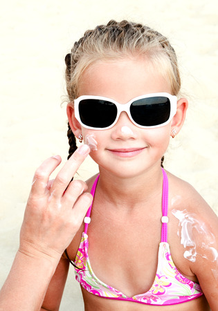 smilie: Mother anoints protective cream to face  little girl on the beach
