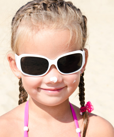 anoint: Cute little girl anoints her nose protective cream on the beach Stock Photo
