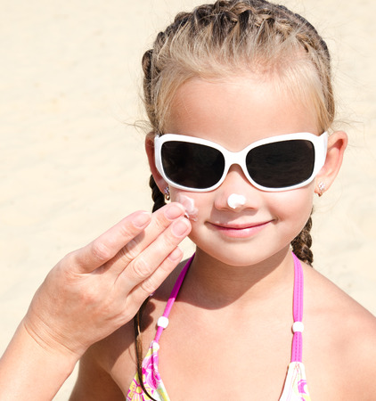 anoint: Mother anoints protective cream to face  little girl on the beach