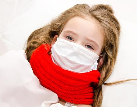 gripe: Ni�a enferma con la mascarilla quir�rgica para la protecci�n contra la gripe de bacterias y virus y la bufanda en la cama Foto de archivo