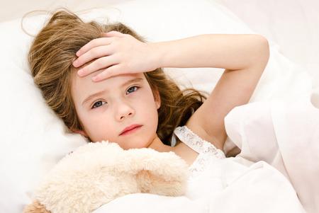 niños enfermos: Niña enferma acostada en la cama con su juguete Foto de archivo