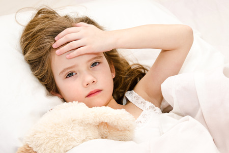 ill: Sick little girl lying in the bed with her toy