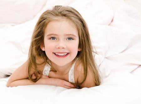 jolie petite fille: Adorable petite fille souriante r�veill� dans son lit