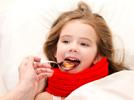スプーンで薬を飲んでベッドで病気の少女 写真素材