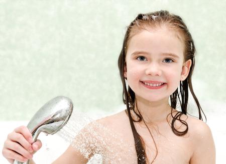 personas tomando agua: Ni�a feliz toma de ducha primer plano en el ba�o Foto de archivo