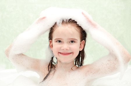 bathwater: Happy little girl washing in bath with foam closeup Stock Photo