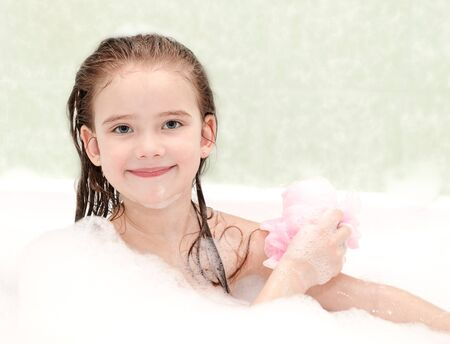 bast: Smiling little girl washing in bath with bast Stock Photo