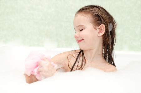 bath: Smiling little girl washing in bath with bast Stock Photo
