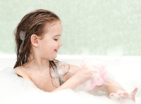bathwater: Smiling little girl washing in bath with bast Stock Photo