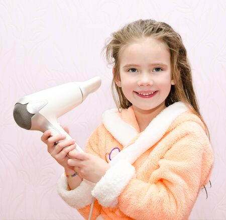 pretty little girl: Cute smiling little girl dries hair isolated Stock Photo