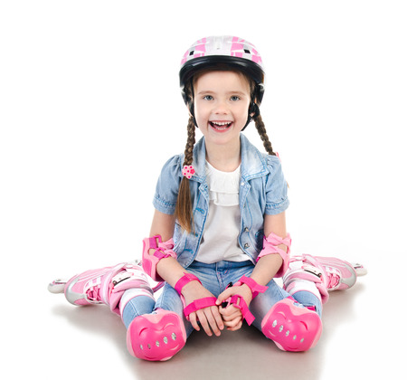 sitting pretty: Cute smiling little girl in pink roller skates and protective gear isolated on a white Stock Photo