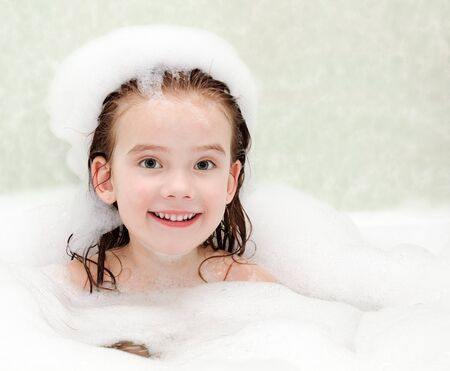 bathwater: Smiling little girl washing in bath with foam closeup Stock Photo
