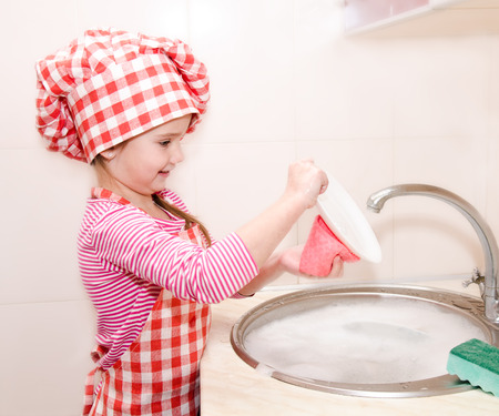Cute smiling little girl washing the dishes in the kitchen photo