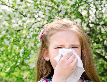 nariz: La niña tiene alergia a la primavera en flor y sopla su nariz al aire libre