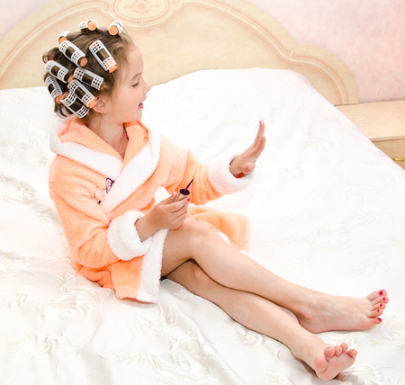 pedicure: Happy funny little girl polishing her nails with curlers in bathrobe on the bed
