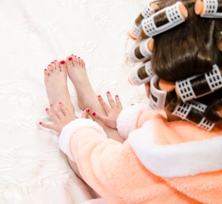 Little girl with manicure and pedicure with hair curlers in bathrobe on bed closeup Banco de Imagens