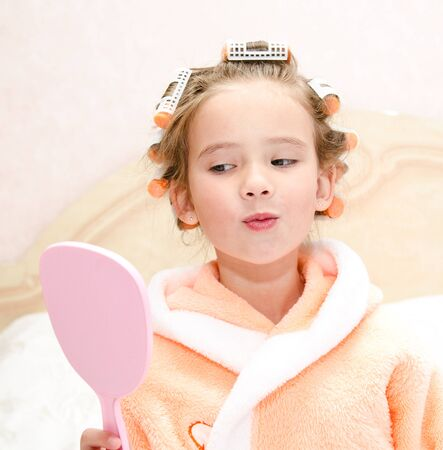rollers: Cute little girl looking at the mirror with hair rollers
