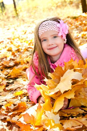 Autumn portrait of adorable little girl with maple leaves outdoor Stock Photo