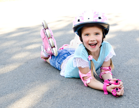 kneepad: Happy little girl in pink roller skates and protective gear outdoor