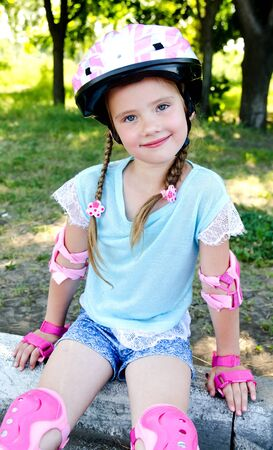 kneepad: Cute smiling little girl in pink roller skates and protective gear outdoor