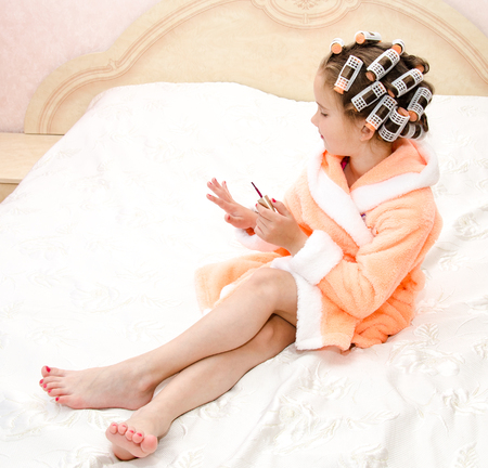 Happy funny little girl polishing her nails with curlers in bathrobe on the bed