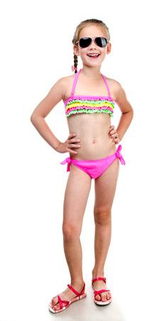 niñas en bikini: Linda niña sonriente en traje de baño y gafas de sol aislado en un blanco