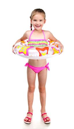 traje de bano: Linda ni�a sonriente en traje de ba�o con el anillo de goma aislado en un blanco Foto de archivo