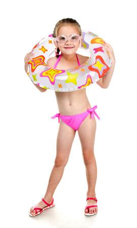 petite fille maillot de bain: Mignon sourire petite fille en maillot de bain et des lunettes avec anneau en caoutchouc isol� sur un fond blanc