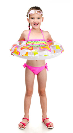 summer wear: Cute smiling little girl in swimsuit and glasses with rubber ring isolated on a white