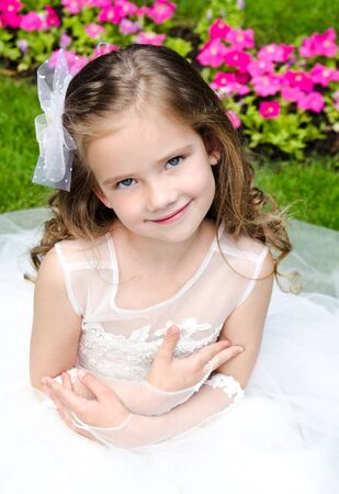 little girl sitting: Adorable smiling little girl in princess dress outdoor