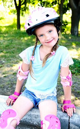 rollerskater: Cute smiling little girl in pink roller skates and protective gear outdoor