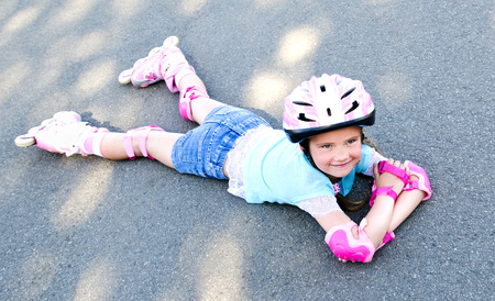 rollerblade: Cute smiling little girl in pink roller skates and protective gear outdoor