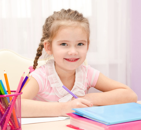 orthography: Cute little girl is writing at the desk at home