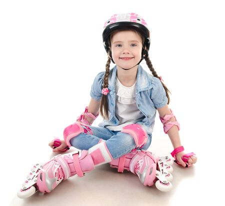 rollerskater: Cute smiling little girl in pink roller skates and protective gear isolated on a white Stock Photo