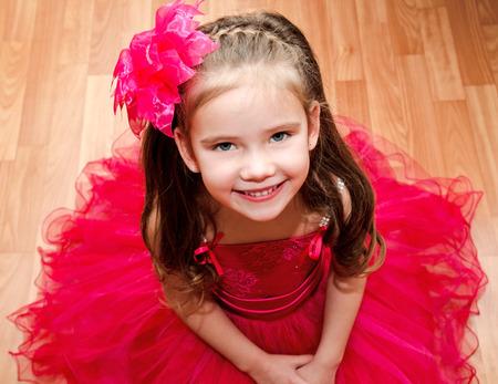 princesa: Adorable niña feliz en vestido de princesa siitting en el suelo