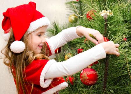 decorating christmas tree: Cute little girl in santa hat decorating the christmas tree