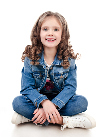model posing: Cute smiling little girl sitting on the floor isolated on a white Stock Photo