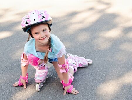 rollerskates: Cute smiling little girl in pink roller skates and protective gear outdoor