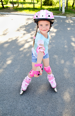 roller blade: Cute smiling little girl in pink roller skates and protective gear outdoor