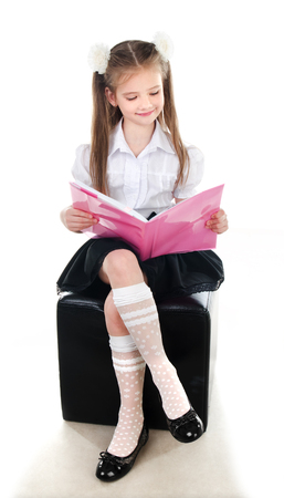 Smiling cute schoolgirl reading the book isolated on a white background