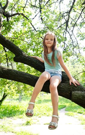 Smiling cute little girl sitting on the tree Stock Photo