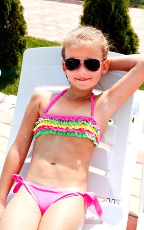 sonnenbaden: Lächelnd kleines Mädchen auf einer Chaiselongue liegen und Sonnenbaden