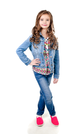 Portrait of adorable happy little girl in jeans isolated on a white